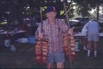 Man Holding Salmon on Stakes 01