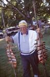 Man Holding Salmon on Stakes 02