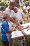 Three Kitchen Volunteers Prepare Salmon