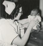 Nursing Student Inspecting Newborn by Unknown