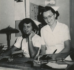 Two Nurses Smiling at Desk by Unknown